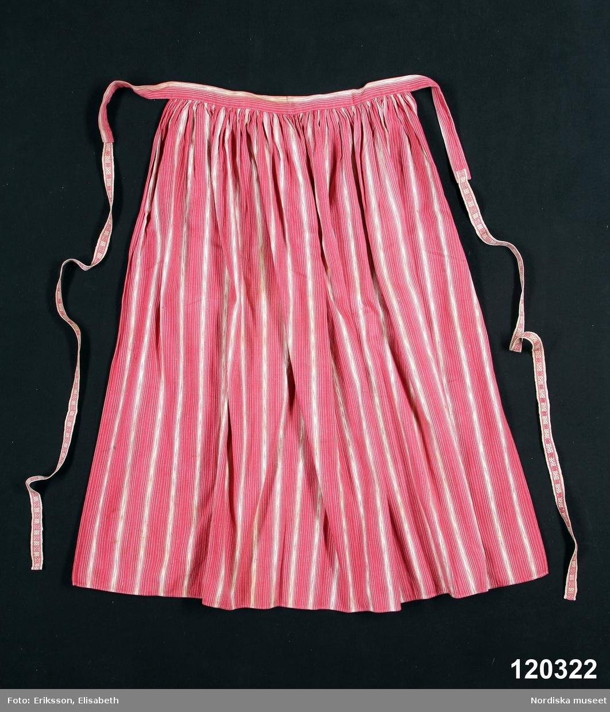 Förkläde i bomull, randigt i vitt på rosa botten med dels smala tvåtrådsrändetr, dels med jämna mellanrum något bredare med  hoptvinnat vitt och rosa garn som ger flamgarnseffekt. . Smala fållar i nederkant och båda sidor, upptill rynkat mot  3 cm bred   midjelinning . Linningen  förlängd med fastsydda 2 cm breda  knytband  av bomull mönstervävda  i rosa på vit ripsbotten. /Berit Eldvik 2012-03-24