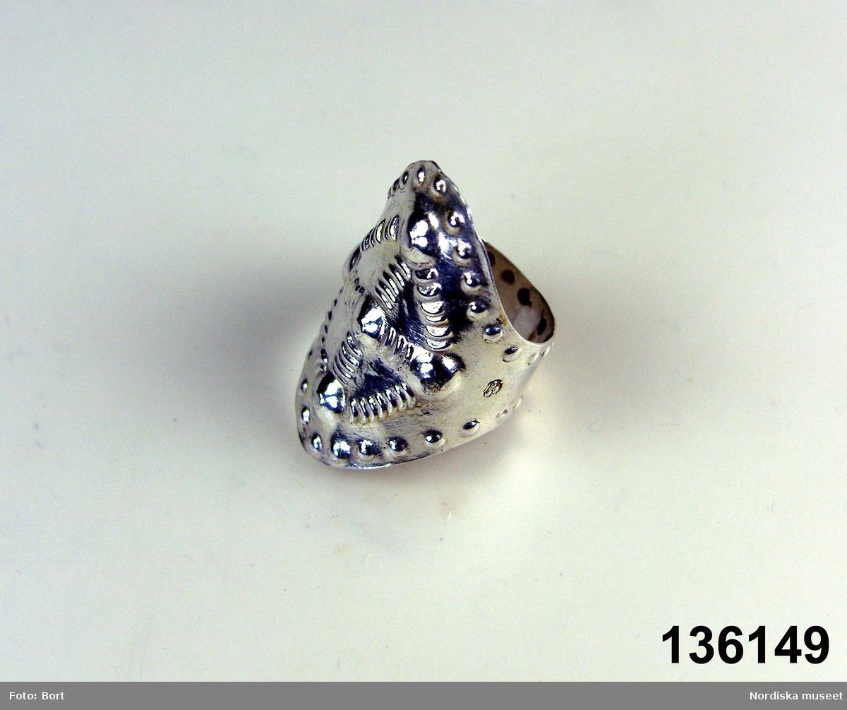 """Huvudliggaren: """"Fingerring av silver, med prässad ornering, bred. Stämplad 'L M K / [tre kronor]"""""""