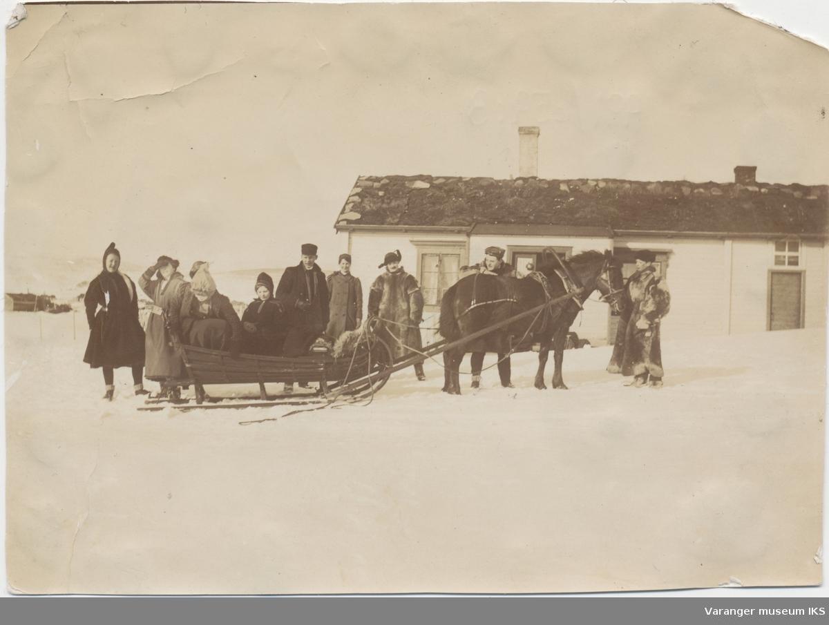 Ti personer ved hest og slede foran et hus eller hytte