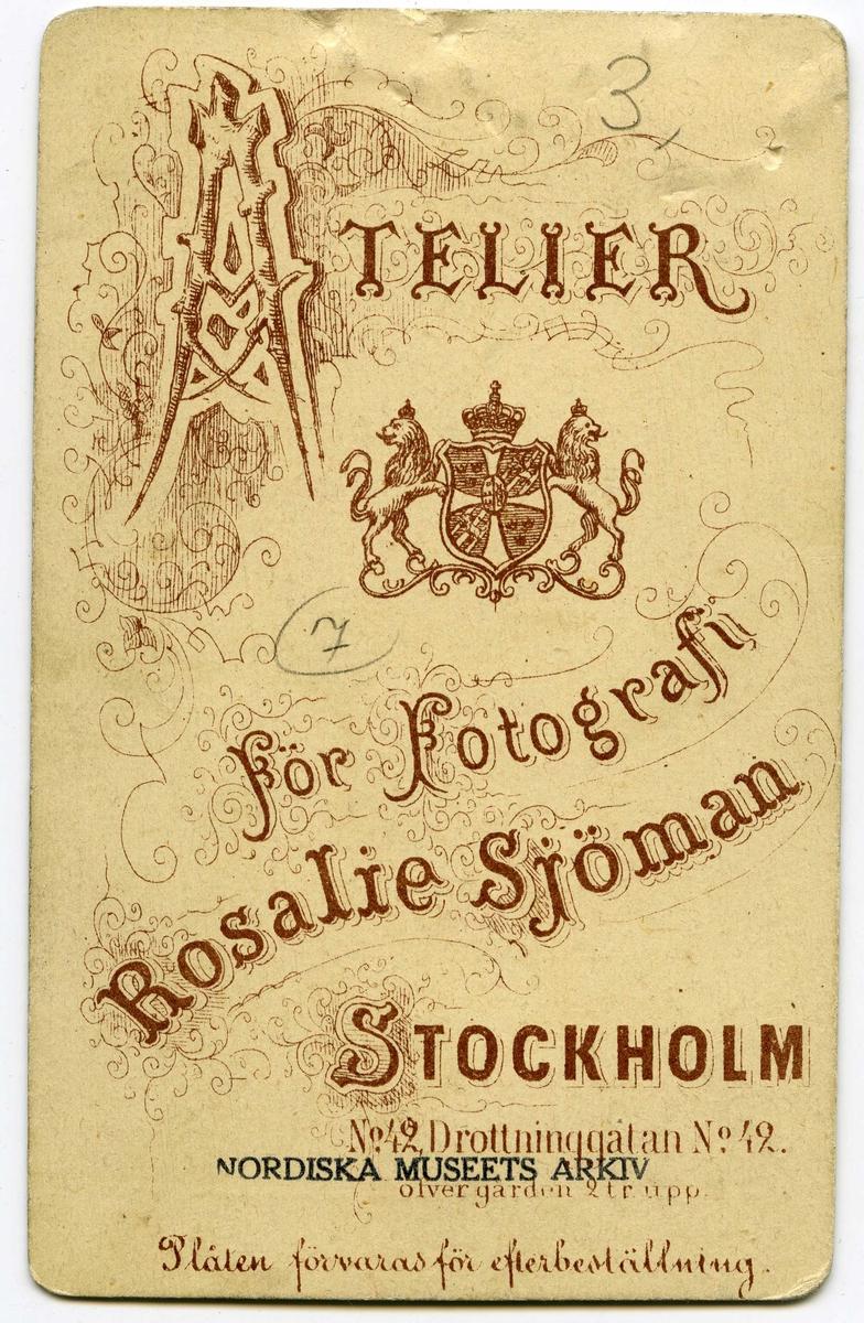 Porträtt av ung kvinna med hög, konstfärdig frisyr med en sammetsblomma som hårsmycke. Kvinnan har en vit skjorta med veckad ståkrage, sammetsband med en kamé runt halsen samt ett pärlhasband och hängande örhängen. 1870-tal.