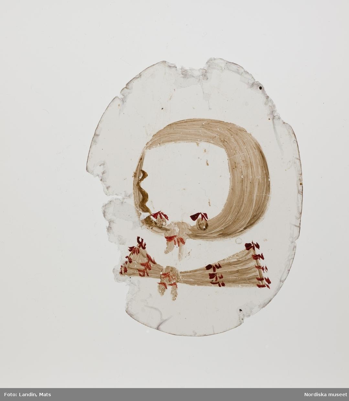 """Katalogkort: """"Miniatyr. Kläddocka/porträtt, olja på kopparplåt i en pressad oval svart läderask, inuti fodrad med ljusblå taft, ligger en kopparplåt med målat kvinnoporträtt, enligt inskription på baksidan - trol. av sent datum - föreställande Drottning Christina. Dessutom finns tretton (13) stycken glimmerskivor, bemålade med olika dräktdelar. Asken med innehåll registrerad som 'Kläddocka'. Ett porträtt med en modejournal. Troligen franskt arbete från 1600-talets mitt."""" Lena Stenberg-Holger 1976."""