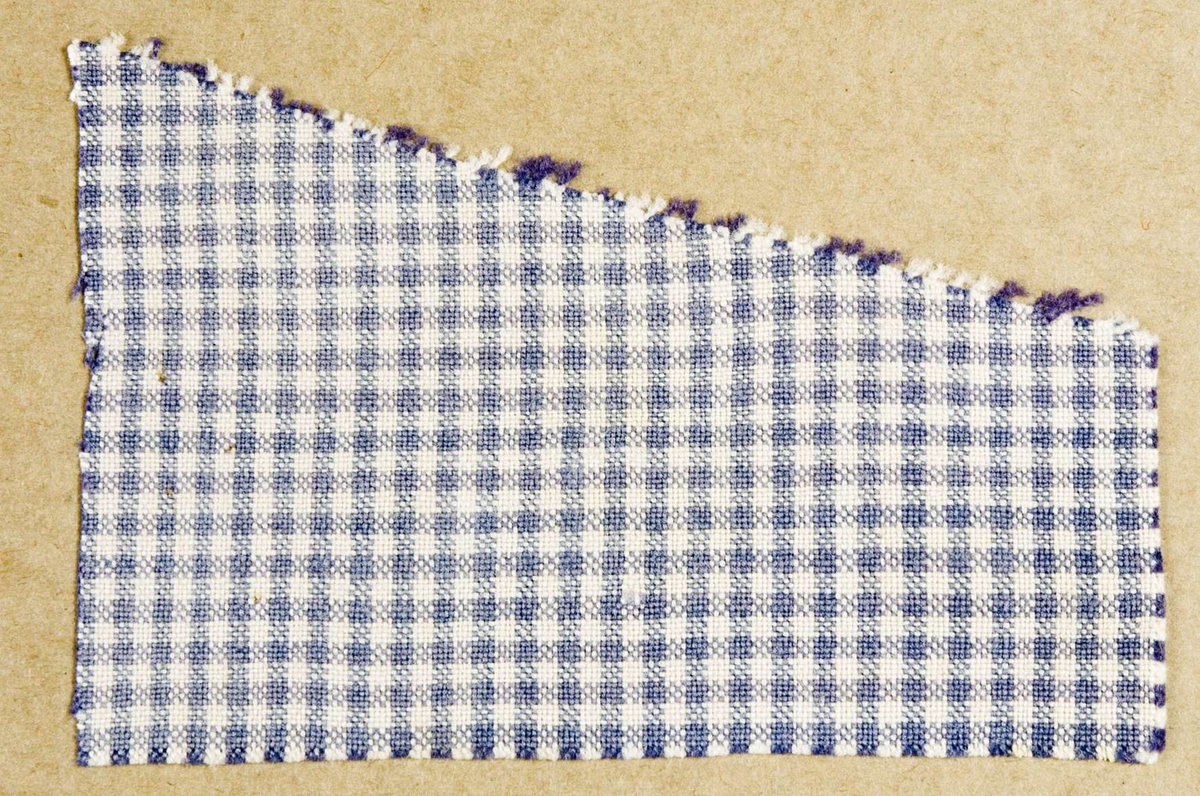 """Vävprov ämnat för klänningstyg vävt i bomullsgarn, tuskaft. Tyget är smårutigt i färgerna vitt och gråblått. Vävprovet är uppklistrat på en kartong i storleken 22 x 28 cm. I övre högra hörnet finns en stämpel """"Uppsala läns hemslöjdsförening"""" och ett handskrivet nummer, """"A.958."""""""