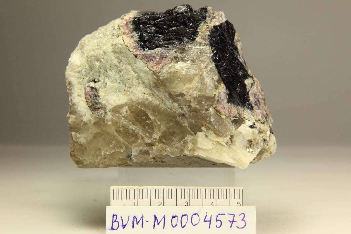 Fluor-elbaitt (rosa) sone rundt fluor-schörl, kvarts, feltspat, glimmer.