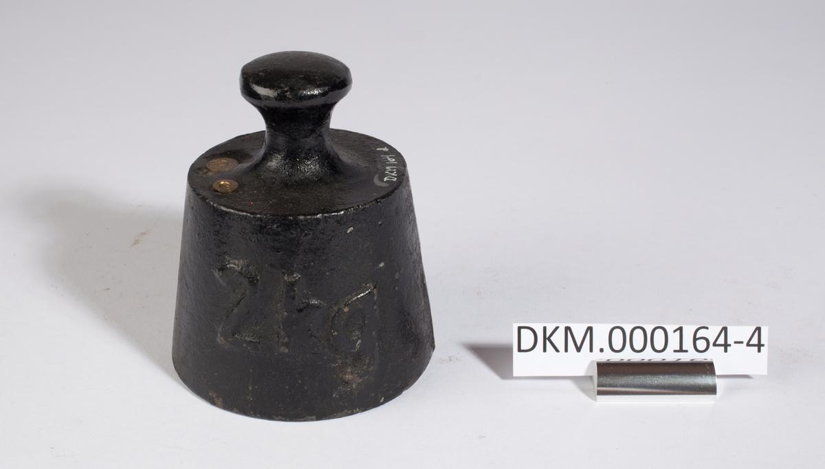 Loddet er formet som en skrå sylinder, det er smalest øverst og har håndtak. Kontrollstempler i loddet.