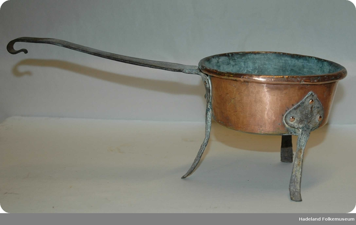 Kobberpotte/gryte med tre bein av jern samt avlangt jernhåndtak.