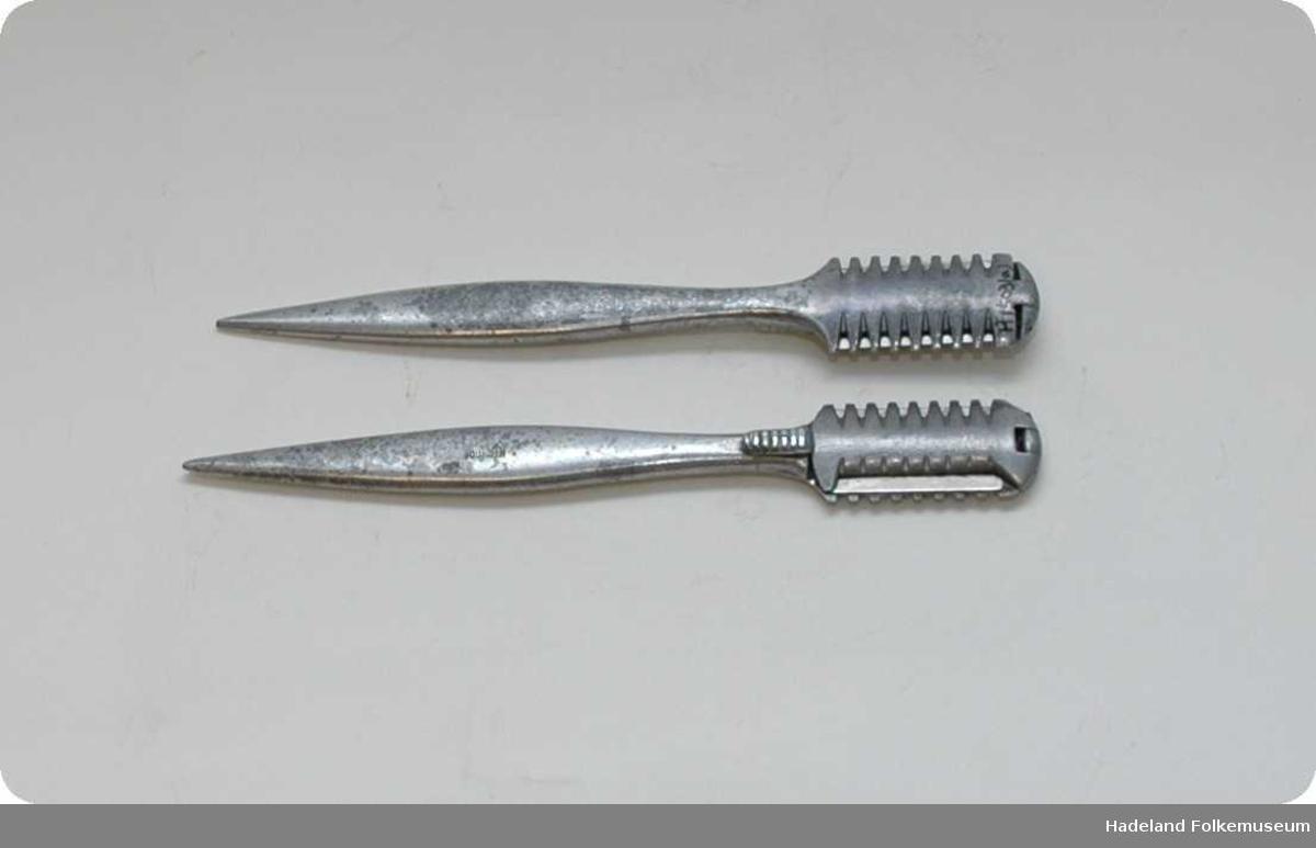 Ovalt, flatt håndgrep med spiss ende. Hodet har feste til barberblad, med tenner.