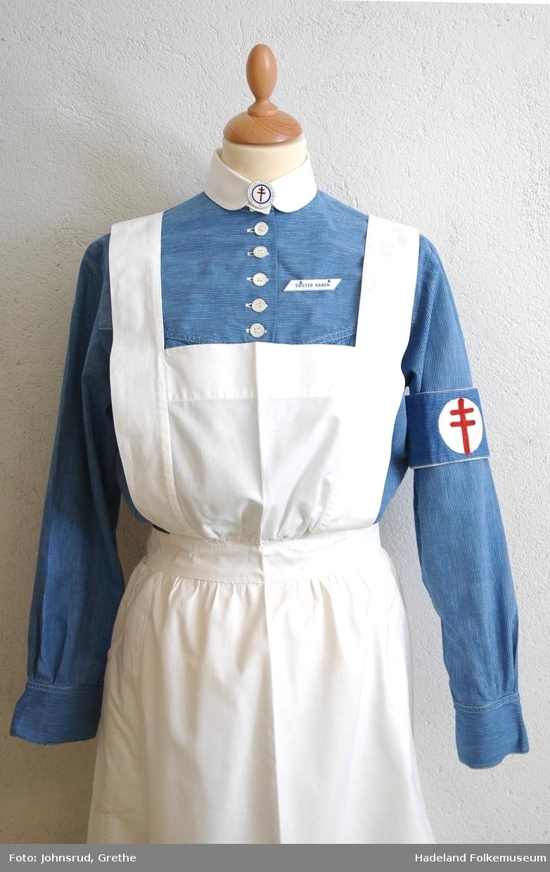 Lorrainekors (lothringenkors) på armbindet. Rødt på hvit bakgrunn. Korset ble tatt i bruk som symbol på kampen mot tuberkulosen f.o.m. 1902