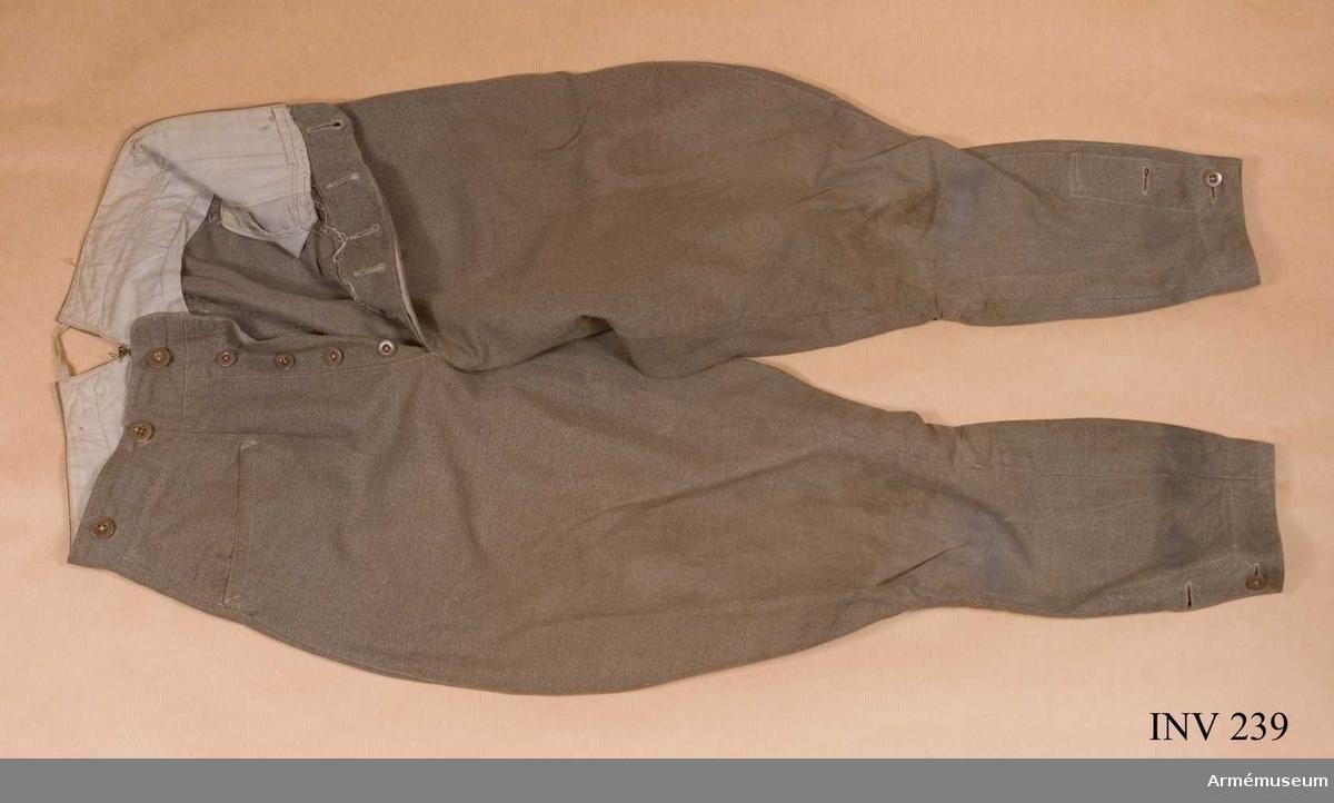 Storlek C 44. Tillverkade av gråbrungrönt bomullstyg och bäres till vapenrock m/1923. De är vida över säte och knä, med ballong slutande nedanför knäet. Sleif i livet, mitt bak. Tillverkad av Arméns Centrala Beklädnads, Kungsholmen,  Stockholm. I midjan en 40 mm bred linning, med fyra knappar på höger del och tre knappar på vänster del. Sprund mitt bak, 75 mm djupt, med band ihophållande flikarna, 60 mm långt.  Framtill sprund, 210 mm långt, gylfknäppt med fyra knappar. Sleif i ryggen, vardera tamp börjande vid sprängvecket i en kil och faststickade 50 mm, övrig längd höger sida 110 mm och vänster 100 mm. Vänster tamp slutar med ett byxspänne märkt PRIMA. Benet knäppes vid vadens utsida med två knappar i ett 130 mm högt sprund. Överdelen går omlott upptill 30 mm och nedtill 20 mm. Två något snedställda fickor på de båda framstyckena. 140 mm breda från sidsömmen mot mitten fram, 160 mm djupa. Ett veck är lagt strax innanför gylfen nedstickat linningens bredd. Infodring i midjan och fickpåsarna i grått bomullstyg. Förstärkta (lagade) mitt bak i sprundet med grå bomullstråd.  Har tillhört framlidne Överstelöjtnanten J.G. Vallquist, I 19. Efter dennes död inköpta av dåvarande Löjtnant A. de Roubetz och har burits av denne vid tjänstgöring i finska armén (frivillig) eftersommaren 1941 (fortsättningskriget). En av knapparna i midjan märkt: Olsson & Sandberg Älfsbyn.