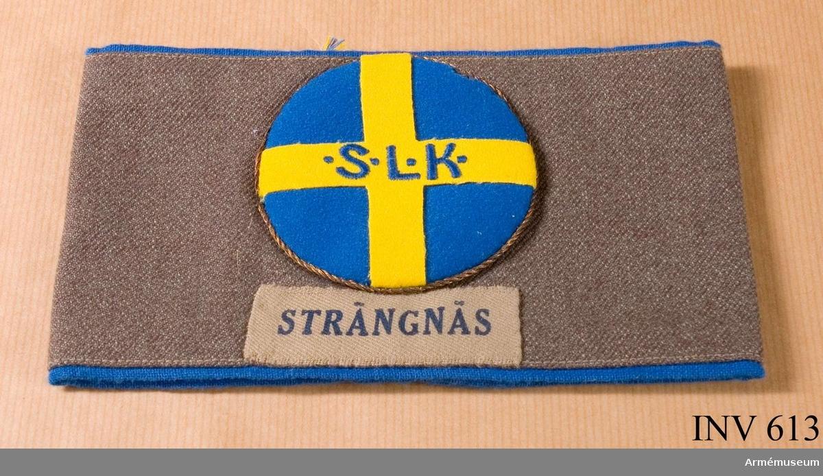 """Armbindel t lottakappa m/1939, SLK Luftvärnet. Två mm bred passpoil av blått bomullstyg, blandat med konstfi- ber, typ flaggduk. Bäres på vänster ärm. SLK:s märke med 70 mm diam (typ större). Tvinnad guldsnodd runt kanten. Blå botten av kläde med gult kors av kläde med broderat med blått silke: S.L.K. (=Sveriges Lottakår). Under märket ett 65 mm långt band, något ljusare än bindeln, på vilket det står tryckt """"STRÄNGNÄS"""" med mörkblå skrift."""