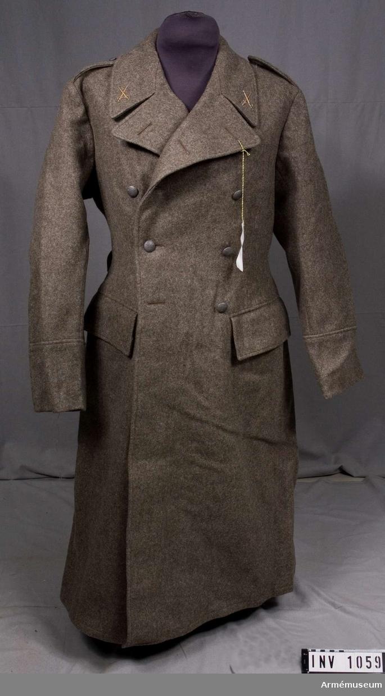 """Stl 96. Av gråbrungrönt kommisskläde. Kavalleriets emblem på  kragen. Manskapsknapp m/1939-1960. Dubbelradig med fem knappar  av mattgrå modell i varje rad. Fem maskintränsade knapphål på  båda framstyckena, längd 30 mm. Kappan är framtill figursydd,  baktill rak. Utan livsöm. Rundskuren krage, slag som kan bäras  hop- eller uppknäppta. Insydda sidfickor med raka lock. Raka,  fasta ärmuppslag, 140 mm höga. Sprund i ryggen, knäppt med två  små knappar och försedda med hyskor för uppfästning. Foder av  grå bomullsdiagonal som räcker till strax nedanför midjan.  Stämplat tre kronor och """"1951, 96"""". Kappan bär på vänster  insida en etikett """"Sydd av Söderbergs, Uppsala"""". Axelklaffarna  är fasta i ärmsömmen och knäppta mot halsen med liten knapp.  Löstagbar ryggslejf, fastknäppt vid sidsömmarna med knapp av  m/större. Alla knappar har refflad botten och försedda med tre  kronor. Kappan tillhör mobiliseringsutrustning vid Armémuseum."""