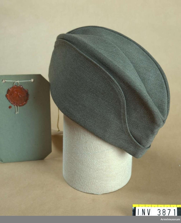 Samma utförande som permissionsmössa m/1939 kommiss. Här dock tillverkad av diagonalkläde.Fastställd 11 maj 1943. Vidhängande etikett från Kungl.  Arméförvaltningen, Intendenturavdelningen, Utrustningsbyrån,  anger att mössan är en tillverkningsmodell.