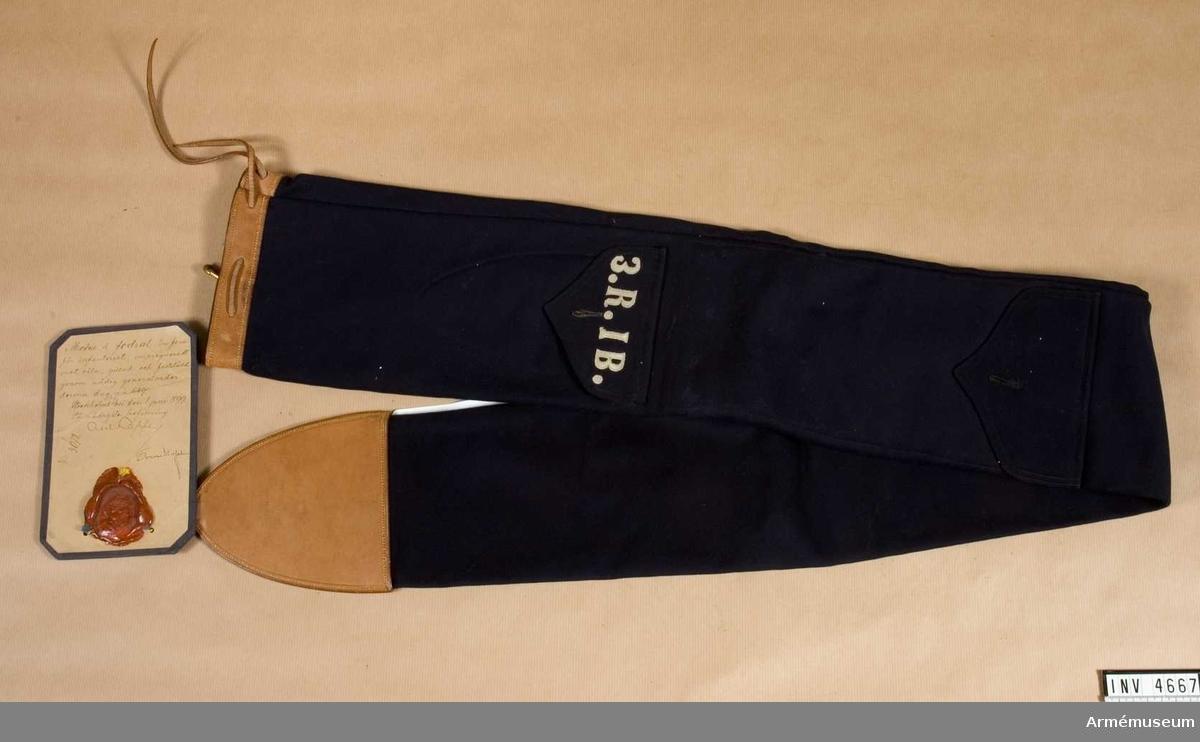 """Av mörkblått kläde. Två fickor m lock. På det ena locket är påsytt i vitt kläde: """"3.R.I B."""", h 25 mm. Fodralet har skinnskoning av ljust läder och dras ihop m skinnrem. Fodrat m vit linnelärft. Vidhängande etikett anger fastställandet."""