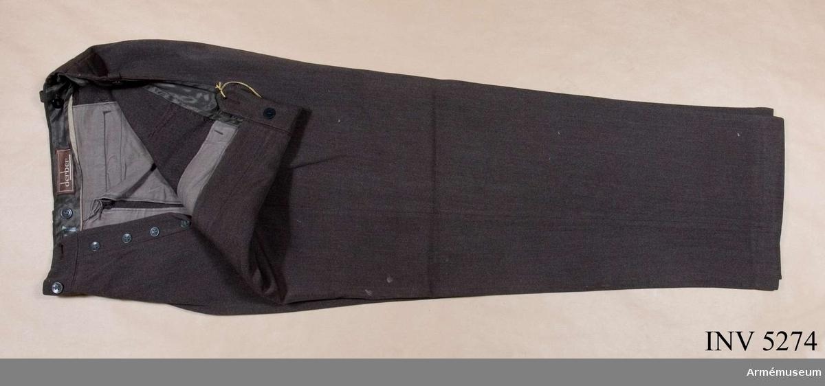 Storlek: C 48. Mörkt gråbrungröna byxor, mörkare än vapenrocken, tillverkade i yllediagonal. Jylfknäppta med hällor i linningen. Sidfickor ooh en bakficka. Daglig dräkt.