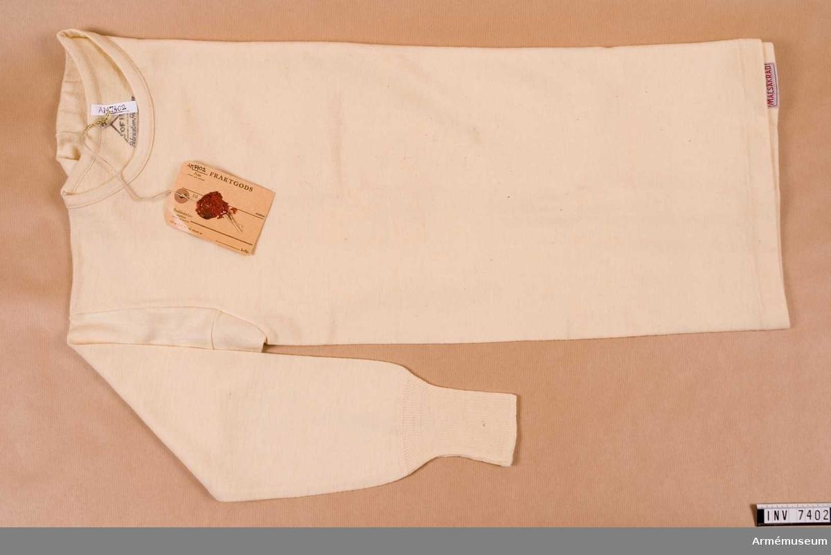 """Helylle, vit. Leveransmodell å skjorta av helylle i vit färg. I nacken märkt 5 SOFIL Fabrication Francise Tourcoing """"Tre kronor"""". Malsäkrad (nedtill).Storlek 5.    Samhörande nr: AM.7403"""