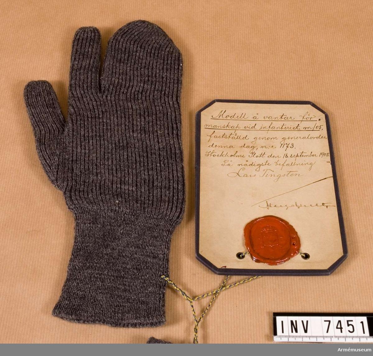 En resårstickad, grå yllevante med tumme och pekfinger fria.   Samhörande par är AM.7450-7451