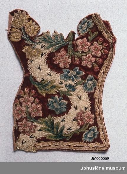 Av blåtonat mörkröd (vinröd) sammet med broderat blommönster gjort av chenillegarn (sniljegarn) i stjälkstygn(?). Både tyget och garnet av silke. Tyget skarvat på ett ställe. Nertill? på baksidan fållat med ett randigt sidenband. Mitt på tyget en böljande slinga i vitt med svarta mönster (ska likna päls?). Över den är naturalistiska blommor strödda. Längs kanten stygnrader fastsydda med läggsöm till en ca 1 cm bred dekoration. Färgerna i blommor och kant är olika nyanser av ljusblått, blåtonat ljusrött och grönt, samt ljusbrunt, gult och beige. Traskanter på två sidor. Dammigt. Något blekt.  Ur Knut Adrian Anderssons katalog: I:25:10  Del av broderi-arbete, silkesblommor på rött sammet, fr. 1700-talet.  Gåva av Göteborgs museum 3/4 1880 genom intendent A. W. Malm.  Ur handskrivna katalogen 1957-1958: Bit av broderiarbete, fr. 1700-t. 1870 Mått: a) 19 x15 cm, b) 10 x 10; a)  blommor i silke på rött sammet; b) silvertråd på rött sammet. Bitarna trasiga i kanterna.  Lappkatalog: 73