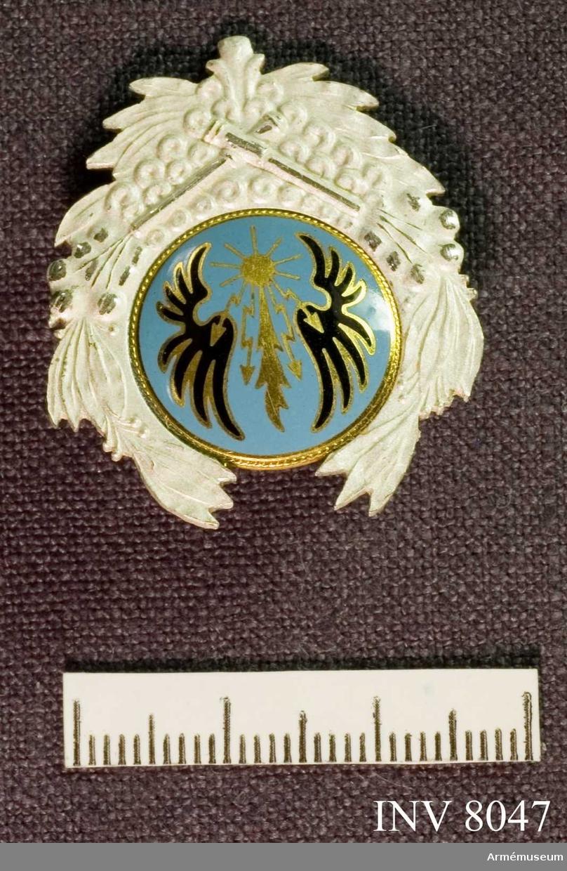 Samhörande gåva är 8020-8047. Höjd 35 mm. Bredd 30 mm. Vikt 20 g. Färg silver, ljusblå, svart och guld. Gott skick 211. Ett silvermärke (vitt) med i mitten ett emaljerat märke i svart och guld på ljusblå botten.