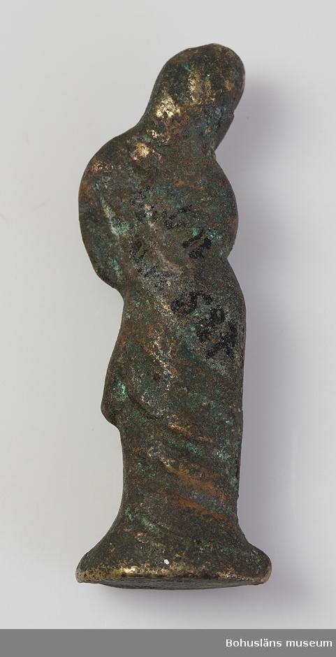 Ur handskrivna katalogen 1957-1958: Husgudomlighet (?) Pompeji. 1883-1886 H. 9. Br 3. Statyett. Kvinno. Brons med spår av gul metallbeläggning. Föremålet helt. Pompeji.  Lappkatalog: 100