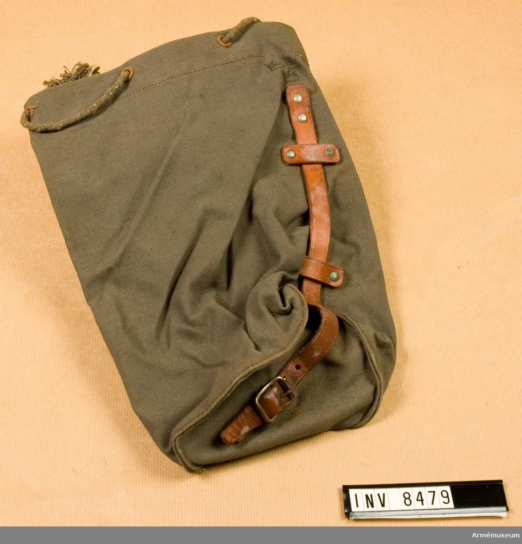 Påse i gråbrungrön smärting. Med dragsko upptill och med rund botten. På ena sidan en läderrem med spänne i bottenplattan. Påsen är kronstämplad.