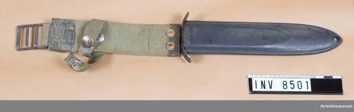 Baljans längd med bäranordning 380 mm. Baljans längd 185 mm. Bredd 40 mm. Baljan av järn, lackerad i svart färg. Bäranordning av väv, i olivgrön färg. Märkt FM/52 P, 1952.  Samhörande AM 8500 fältkniv fm/1952 p, AM 8501 balja till fältkniv fm/1952 p.