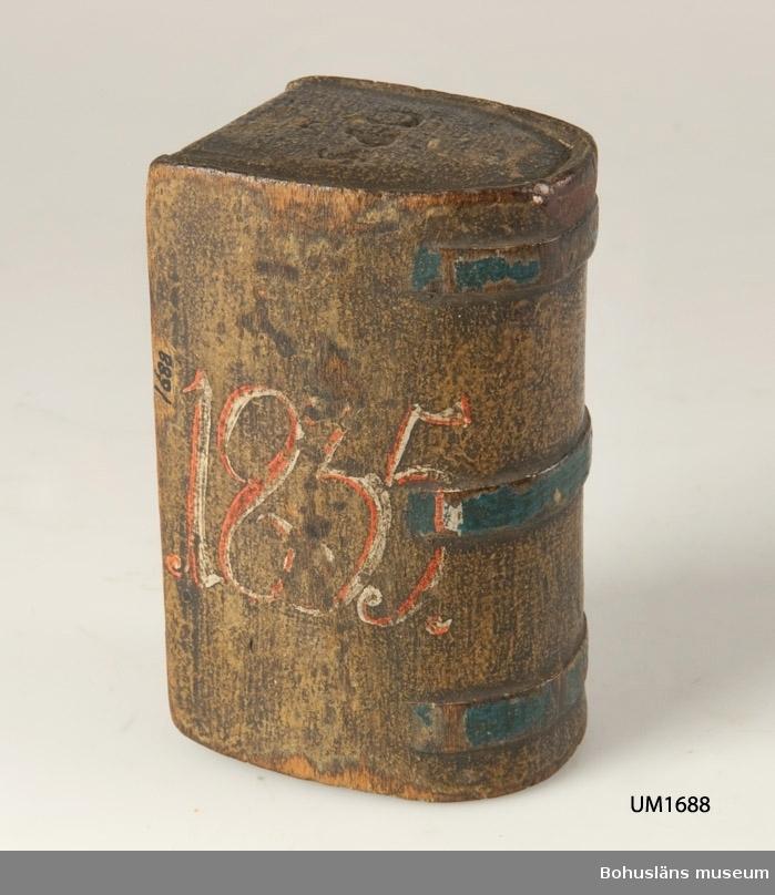 """Liten rundad lådform (psalmboksformad) med skjutlock. Grönmålad inuti. Locket har två tvärgående band i relief. Målad dekor med blomslinga i rött och grönt på ockrafärgad botten. Blå rand på reliefen och röd kant på en av kortsidorna. Tre tvärgående blåmålade band i relief på den välvda långsidan. """"O.P.S 1835"""" målat i rött och vitt på framsidan. Texten finns inskuren på båda kortsidor. Färgen är till stor del bortnött och har mörknat betydligt. Trolig friargåva med tanke på inskurna årtal och skrivna initialer.  Litteratur: Knutsson, Johan, Friargåvor, Nordiska museets förlag, Stockholm 1995. Gjaerder, Per, Esker og tiner, C. Huitfeldts förlag, Oslo 1981, s. 53-55.  Ur handskrivna katalogen 1957-1958: Psalmboksformad dosa av trä Mått a) 10,5 x 6,5 x 5,3 cm """"OPS"""" """"1835""""; vackert målad i gulbrunt o. blått, m. inskr. i rött o. vitt; hel.  Skjutlocket b) 9,7 x 4 cm  Lappkatalog: 84"""