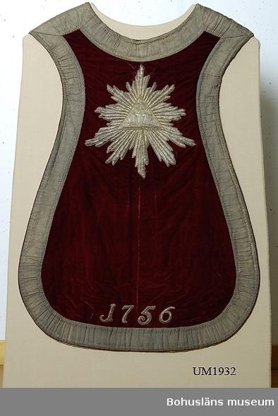 """Föremålet visas i basutställningen Uddevalla genom tiderna, Bohusläns museum, Uddevalla.  Mässhake från Uddevalla kyrka i röd sammet; påsydda band vävda av förgylld metalltråd. Broderat krucifix; förgylld metalltråd. Under krucifixet broderade initilalerna A.K:B.B:N.H  Ur handskrivna katalogen 1957-1958: Mässhake, U-a kyrka H. 94 resp. 116 cm. Röd sammet m. guldstickn; mont. å vitt tyg, insatt i glas och ram; ramen: 136 x 90 cm. """"A.K:B.B:N.H"""" """"1756"""".  Lappkatalog: 12"""