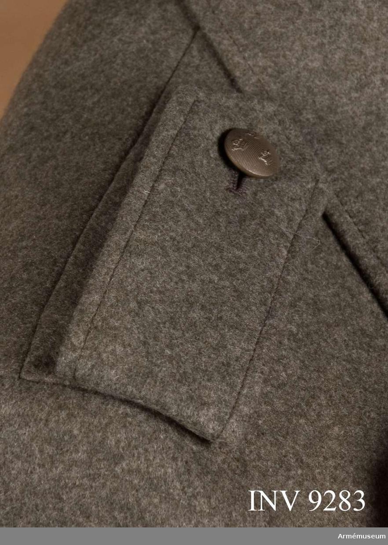 Till jacka för kvinnlig krigstjänstpersonal. Av gråbrungrönt kommisskläde med knapp och knapphål för knäppning runt tränsar på jackans axel. Axelklaffen viks  dubbel och är fodrad med gråbrunt kläde. Knapp av mindre  modellen och tillverkare Sporrong.