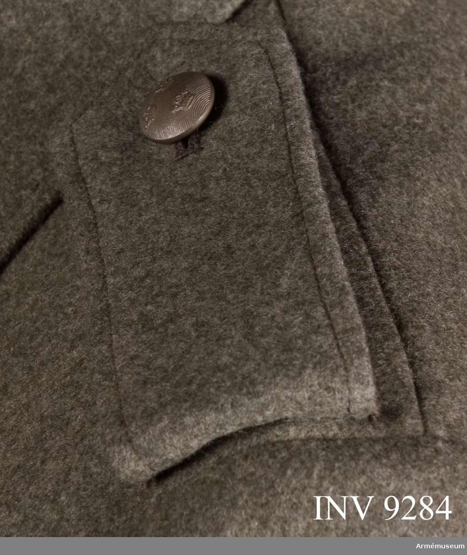 Av gråbruntgrönt kommisskläde med knapp och knapphål för knäppning runt tränsar på jackans axel. Axelklaffen viks dubbel och är fordrad med gråbrunt kläde. Knapp av mindre modellen och tillv. Sporrong.