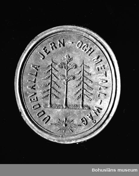 """Ur handskrivna katalogen 1957-1958: Sigillstamp """"U-a Jern- o Metall-Wåg"""" Oval stamp, mått: 31, x 2,2 cm, av mässing; skaft av ljust polerat trä. Hel.  Lappkatalog: 36  Stämpel för UDDEVALLA JERN- OCH METALL-WÅG"""