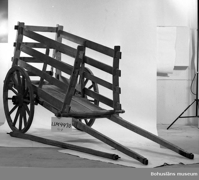 Ur handskrivna katalogen 1957-1958: Hökärra Kärrans botten, a), m. skaklar och järnaxel f. hjulen. L. 400; axelns L. 128,5 cm. Hjulen b) och c) b) D. 107; c) D. 107 cm; rödmålade, m. järnringar. d) 0ch e) sidohäckar, mått: 211 x 115 cm 211 x 115 cm. f) gavelhäck. 112 x 87. Föremålen hela. g) en stång av trä, m. en järnspik i ena och en järnbygeli andra ändan L. 256 cm. Hel.  Lappkatalog: 40