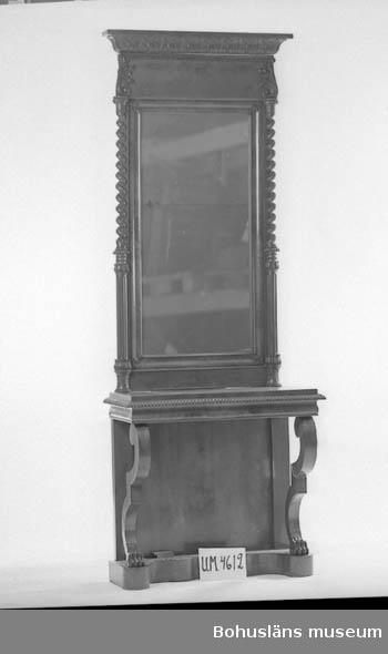 Föremålet visas i basutställningen Uddevalla genom tiderna, Bohusläns museum, Uddevalla.  Spegel och tillhörande spegelbord, två lösa delar. Spegeln omgiven av två kolonner, nedre tredjedelen med kannelyrer. Övre 2/3 av kolonnerna spiralvrida och med närmast palmettprytt kapitäl. Nedtill kolonnbaser och rektangulärt fält. Uppåt avslutning med förkroppad palmettprydd rak list. Delat spegelglas, mahognyfaner på blindstä av furu. Hela spegelbordet mahognyfanerat på blindträ av furu hel bottenplatta,helt ryggstycke, profilerade och böjda framben med lejontassar. Bottenplattans framsida profilerad. Möbeln med biedermeierkaraktär.  Litteratur: Granat, Stellan. Kring Carl Fredrik Richters porträtt av Anders Gottfrid Krok och hans familj. Bohuslän årsbok 1997.  Ur handskrivna katalogen 1957-1958: Golvspegel Spegel med bord. - Brunbetsad? träinfattning Spegelns L. 162 Br 86,8. Föremålet helt. Bordet: Brunbetsat trä. L. 91. Br. 45,5. Föremålet helt. H: c:a 84  Lappkatalog: 82