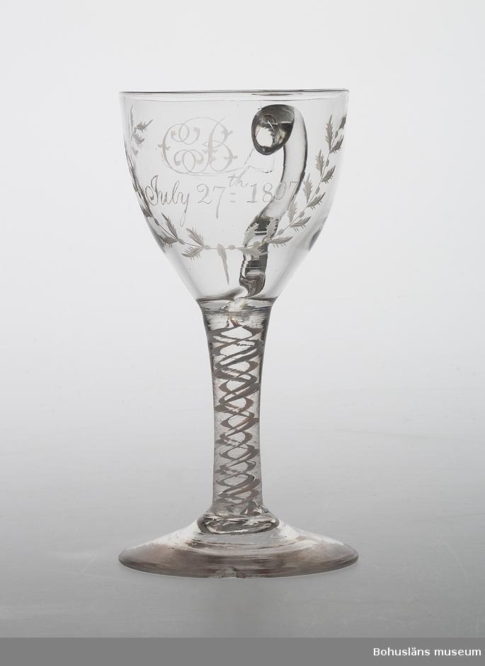 """Glas på fot med öra. Rund fot. Glasets ben har spiraler i vitt; """"latticinospiraler"""". Foten något defekt; sprickor i kuppan. Engelsk tillverkning."""