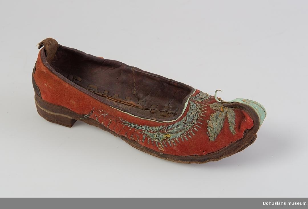 Ur handskrivna katalogen 1957-1958: Två st. skor, udda a) Sulans l. c:a 30,5 cm. Uppvikt i tån. Av läder m. broderier i metalltråd.  [På foto] b) Sulans l. c:a 27,5 cm. Lädersula; rött tyg m. broderier. Hel.