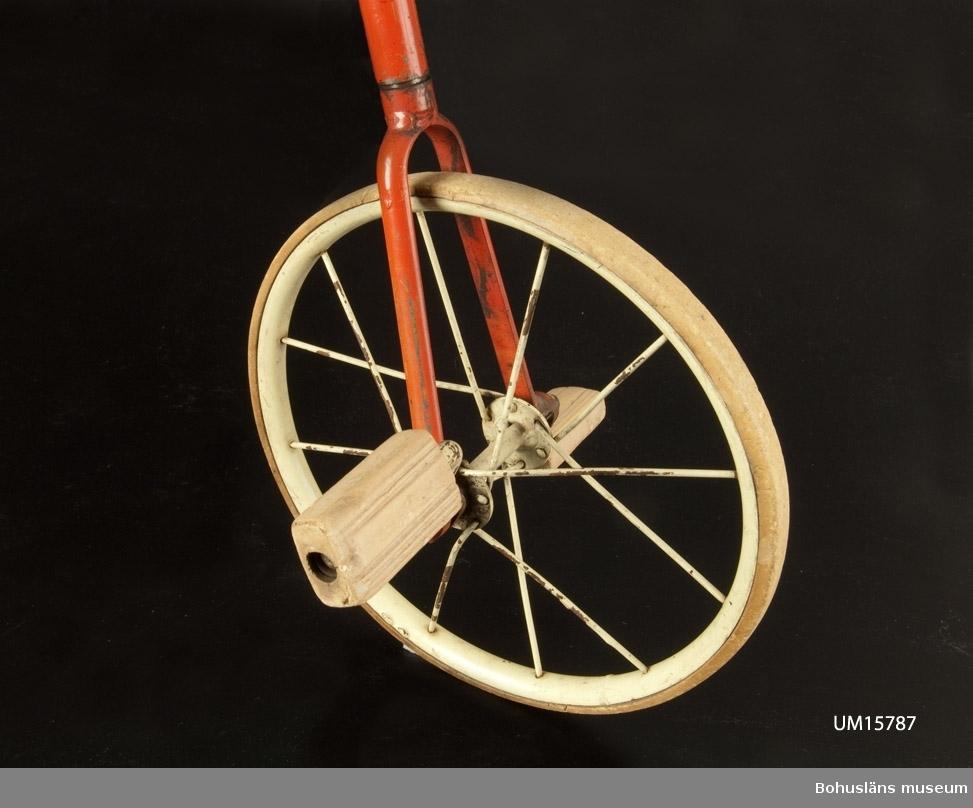 Trehjulig barncykel med röd stomme, vit sadel och pakethållare. Gummiklädda handtag, trampor av hårdgummi.