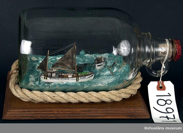 Flaskskepp, båtarna fastsatta i kitt på botten av flaskan, som är  tillsluten med kork. Mellan flaskan och bottenplattan finns ett rep lindat. Motivet eller scenen i flaskan föreställer Dalarö av Hönö, minsprängd nordväst Hirtshals den 9 mars 1945. Beatrice av Knippla bärgade 2 man av besättningen, fyra man omkom.  Litt:  Edvardsson, Dag, Åberg, Georg: De hade inget val.