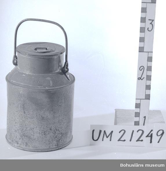 """594 Landskap BOHUSLÄN  3-liters mjölkflaska. Cylindriskt kärl med en smalare, kort hals samt rörligt bärhandtag. Lock med hänkel. Mässingsskylt med instansad text: """"HASSELBERGET"""". En trea (3) instansad vid halsen. Föremålet är korroderat.  Omkatalogiserat 1997-01-13 GH.  UMFF 4:5"""