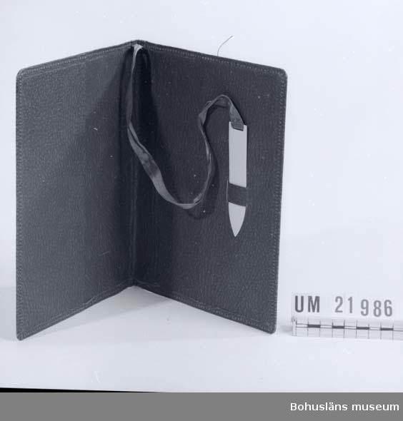 410 Mått/Vikt ! TJ 0,8 CM 594 Landskap BOHUSLÄN  Bokomslaget är av svart, grön, melerad väv på papp. Ett vitt celluloidbokmärke i form av en nagelfil. Fastsytt i blått sidenband.  UMFF 70:10