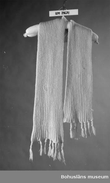 Rosa. Fransar på kortsidorna. Inkom i samband med upprop i april 1984 om kläder till 1960-talsutställningen i museet.