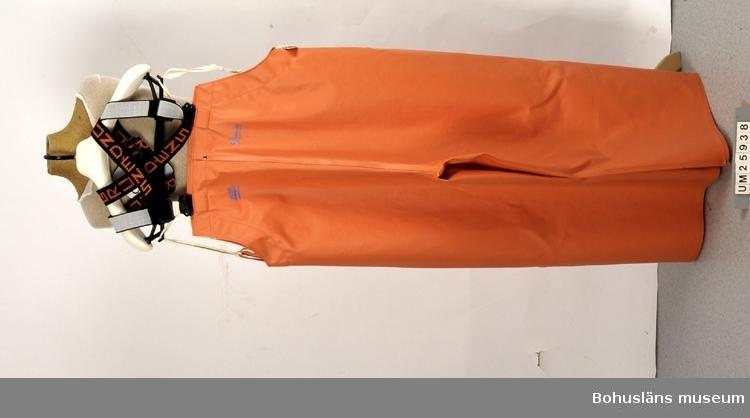 """Föremålet visas i basutställningen Kustland, Bohusläns museum, Uddevalla.  Regnställ, arbetsplagg för fiskare. UM025938 byxor och UM025939 jacka. Gjord av smärting (extra kraftig bomullsväv), som av ett portugisiskt företag beläggs med mjuk och smidig PVC-plast. Plaggen sys och sorteras vid Grundéns Regnkläder AB:s fabrik i Lissabon. Sydvästen används knappast alls av nutida fiskare, som istället fäller upp jackans huva. Regnstället fabriksnytt när det skänktes till museet. Byxorna når upp på överkroppen, försedda med elastiska, svarta hängslen med invävt """"Grundéns"""". På den orange byxan upptill tryckt """"Grundéns of Sweden"""", samt ett segelfartyg, den femmastade barken Köpenhavn, samt """"Herkules"""", modellnamn på byxan. Se även tillhörande jacka UM025939. Tillhörande lapp med produktionsinformation och skötselråd. Företaget startades i Grundsund 1926. I början av 1950-talet flyttade man till Uddevalla och inrymdes då i gamla tändsticksfabrikens lokaler mot Kungsgatan. På 1970-talet flyttades tillverkningen utomlands. Ett helägt dotterföretag startades i Lissabon. Företaget säljer till Europa och i USA."""