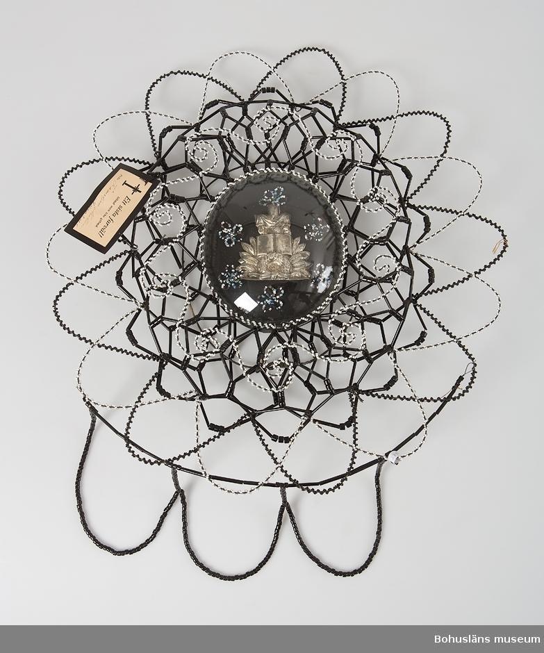 """Oval krans gjord på stomme av järntråd i en konstfull hopflätning, den inre delen i två våningar. Stommen är klädd med uppträdda glaspärlor, svarta stavformade och runda, samt med  vita och svarta små pärlor, uppträdda på textil tråd som virats runt stommen. Kransens mitt pryds av en silvermålad pappdekoration som vilar på en platta av tunn plåt och papp. Dekorationen är utformad som  i form av ett draperat kors på ett arrangemang av smalflikiga blad med en krans och en uppslagen bibel. Runt pappdekorationen sitter sex blomsterliknande utsmyckningar av små uppträdda glaspärlor i vitt, svart, grönt, blått och ofärgat glas och detta ligger skyddat  under en oval glaskupa. I kransens nederkant hänger tre girlander gjorda av avlånga glaspärlor trädda på textiltråd. I kransen sitter fästad ett svartkantad papperskort med tryckta texten:  """"Ett sista farväl! Gömd men icke glömd. Från Familjen Mattsson Ängarne"""" (handskrivet).  Järntråden bitvis rostig.  Ur följebrev, skrivet av Rune Hammarskog, yngre bror till den avlidne: """"Pärlkransen och pärlkorset har förvarats på en vind i ett hus i Håvedalen, Norra Bohuslän. Kransarna och korset var tillägnade gossen Holger Hansson, son till Ester och Hans Nilsson, Håvedalen. Holger var född den 22 april 1917 och avled den 16 september 1928, alltså 11 år gammal. Begravningen ägde rum i Skee kyrka någon vecka efter dödsfallet. Kransen överlämnades då av Holgers morföräldrar, f.d. gränsridaren Olof Martin Carlén och hans hustru Emma. Givaren av korset är okänd. Vid samma tillfälle lämnades även en pärlkrans av en granne till familjen, snickaren Anton Mattsson och hans hustru Maria. Anton Mattsson hade troligen även tillverkat Holgers kista. På Skee kyrkogård fanns i slutet av 1920-talet och början av 1930-talet ett flertal gravar som var prydda med pärlkransar/kors. En del kransar förvarades i en trälåda som var täckt av en glasskiva. Kransarna var ömtåliga och skadades ofta. De togs därför bort och försvann så småningom helt från kyrkog"""