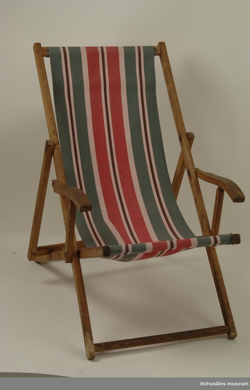 """Uppfällbar/ihopfällbar solstol med armstöd. Klarlackad täram med välarbetade detaljer. Randig markisväv i rött, grönt, vitt och svart (möjligen tidigare blått). Originaltyg.  Detta är den ena av två solstolar. Se fotografi UMFA55058:0007.  Föremålen har använts i en sommarstuga i Sundsandvik, Uddevalla kommun. I förvärvet ingår också reprofoton från familjens fotoalbum med fotografier från somrarna i Sundsandvik, se UMFA55058. Givarens morföräldrar, lärarparet Erik Abrahamson (1890-1973 och Judith Backman (1888-1957) med två vuxna döttrar lät bygga stugan 1939. Tomten inköptes 1938 på mark som ägdes av Arvid Jacobsson som innehade en av """"De tre Sundsgårdarna"""" i Sundsandvik. Dessförinnan hyrde familjen under två somrar hos """"baderskan Klara"""" i Sundsandvik. Under några år semestrade familjen också på pensionat i Rävlanda och Kavlanda då man hyrde för en månad per säsong.  Familjen bodde i Göteborg och reste med ångbåt upp till Sundsandvik vid Nötesund och steg av på den ångbåtsbrygga som då fanns här. Sedan Bohuslänska Kusten lagt ner skärgårdstrafiken (1956?) for man med tåg till Uddevalla och polletterade då godset. Till Uddevalla reste man med tåg och sedan vidare med buss som stannade vid macken på Sundsandvik.   Sommarstugan är ett en- och ett halvplans hus med brunmålad panel och blå snickerier på en högt belägen naturtomt med vid utsikt över farvattnen vid Nötesund, Koljön och Havstensfjorden. Färgsättningen ansågs vid tiden vara bohuslänsk, """"i bohuslänska färger"""".  Huset är i stort sett oförändrat sedan byggtiden. Huset har en storstuga med öppen spis, fernissade trägolv, två sovrum och ett kök med platsbyggd inredning. På övervåningen två gavelrum och en öppen men inredd vind. Redan från början fanns egen grävd brunn för rinnande vatten samt ett kombinerat utedass/vedbod. El måste också ha funnits från början eftersom man hade elspis. Kylskåp sattes in på 1960-talet. Under de första decennierna och in på 1970-talet satsades en del på trädgårdväxter med pionbus"""