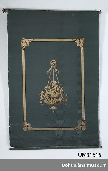 Rullgardin, rektangulär med målad både fram- och baksida. Blå botten med schablonmålning i guld och detaljer i brunt och svart som består av en hängande ampel fylld av frukt och blad med en rosettknapp och girland i upphängningen. Ampeln är inramad av en rak ram med profilerade och dekorerade hörnen. Väven är fästad med metallnubb i trästänger upp- och nertill. Upphängning i  trästång upptill med utstickande järntenar och svarvade trätrissor, den ena saknas. Nertill svarvad tunnare trästång. Ett grövre schablontryckt band 8 mm brett (en väv) med tryckta små figurer sitter som förstärkning där spikarna går in i stången.  Snodd saknas. Fuktfläckar.  Rulllgardinen har använts av Anna Kristina Olofsdotter (1830 - 1921).  Hon var dotter till Olof Johansson och Johanna Larsdotter från Näs i Myckleby socken på Orust, Bohuslän. Anna Kristina gifte sig 1858 med skutskepparen Edvard Olsson (1834 - 1872) från Stranden under Kåröd i Myckleby socken. Paret hade två söner, den ene dog vid ett års ålder, den andre föddes 1866. Då maken Edvard dör måste Anna Kristina sälja bohaget på auktion för att kunna lösa utestående fordringar. Auktionen inbringade 883,70 riksdaler Rmt. För att rädda det nödvändigaste till hushållet nödgades änkan ropa in för 136 riksdaler Rmt. Hon köper också mangårdsbyggnaden och en enkel ladugård. Den sexårige sonen ärvde hälften av boets behållning, resten gick till mannens släktingar. Sonarvet förvaltades av en förmyndare. Sonen blev sjöman och avhördes sista gången 1886, då som förrymd jungman i Boston, USA.  Som änka försörjde sig Anna genom att ge varma tångbad för 16 shilling badet, (se UM031466 Badkar) och med att hjälpa till på gårdarna vid behov. Hennes hyra för tomten var 7 kronor om året. År 1921 dog Anna 91 år gammal och hon hade då levt som änka på Heden i 49 år. Heden blev därefter öde, huset såldes till Totorp där det sattes upp som drängstuga.  Rullgardinen har brukats i givarens föräldrahem.  Litteratur: Myckleby socken, del 5, s. 84.