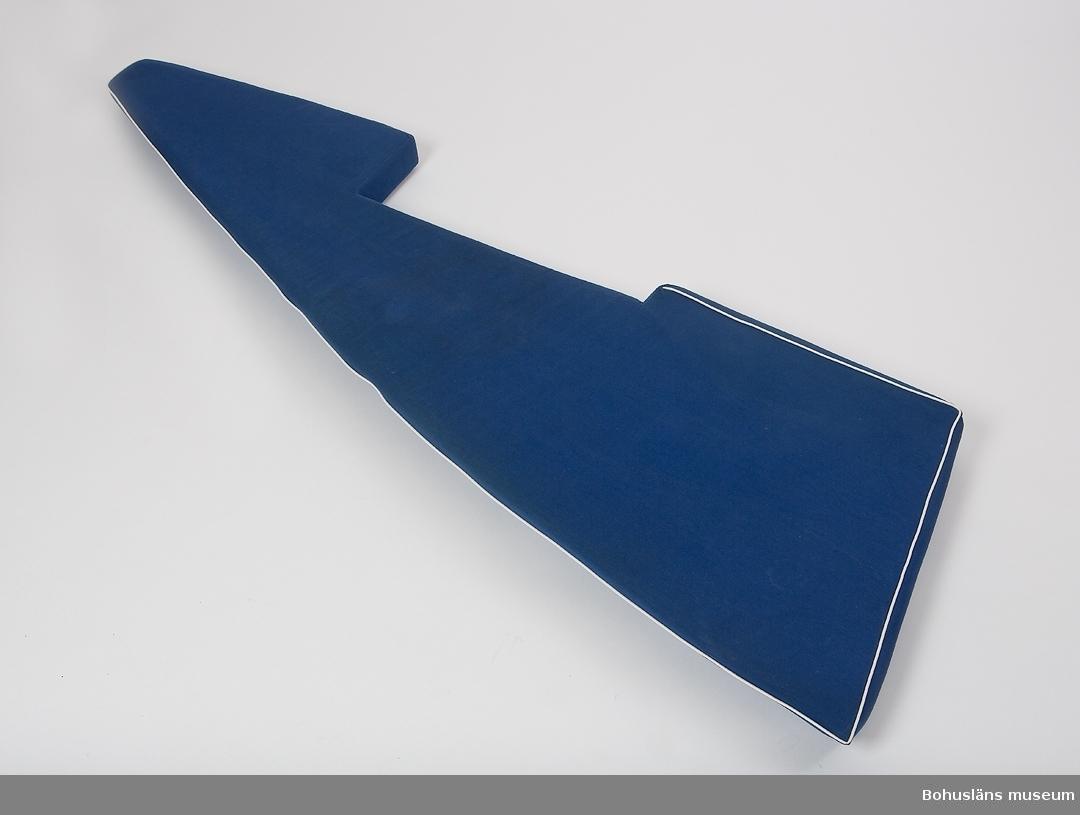 Madrass för styrbords koj  i förpiken. Formskuren skumgummidyna klädd med mörkblå kanvas. Övre kanten skodd med vit plastpasspoal. Fläckar av saltvatten, något blekt.  Vindö 22 nr 10 ANNOVA levererades sommaren 1968.  ANNOVA är en fin representant för övergången från trä till plast inom båtbyggeriet. Skrovet är tillverkat i glasfiber, men däcket är av teak, och överbyggnad och inredning av mahogny.  Trävirket och hantverket är av högsta kvalitet. Skrovlängden är 7,10 m och bredden 2,15.  Masten är av aluminium. ANNOVA är fortfarande i originalskick.  Hon har hela tiden haft en och samma ägare,  professor Carl-Gustav Engström med familj.  Vindövarvet, ett av Orustområdets legendariska båtvarv, startades 1926 av Carl Andersson.  Han var både en skicklig hantverkare och konstruktör.  Varvet byggde olika bruksbåtar, men med tiden satsades allt mer på kappseglingsbåtar. Under 1950-talet var Folkbåtar den stora produkten. Just Folkbåten hade blivit en omtyckt familjebåt.  Men många ville ha en något större båt som passade bättre för havssegling. Det ledde till att Carl 1961 konstruerade en båt kallad Vindö 28. Den blev en milstolpe i varvets historia och var den första i raden av olika Vindöbåtar som gjorde varvet välkänt i både Sverige och utomlands.  Erfarenheter av plast fick Vindövarvet från 1960, och det nya etablerades på allvar när man 1965 började producera Vegan. Den var konstruerad av Per Brohäll, och blev oerhört populär. Plastskroven gjordes inte på Vindövarvet, utan köptes in från Lysekils Båtvarv, senare från Lyse Plastprodukter. När Vindö 22:an levererades hade Carls son Karl-Erik Andersson övertagit uppgiften som varvets ledare, men Carl satt kvar vid ritbordet.