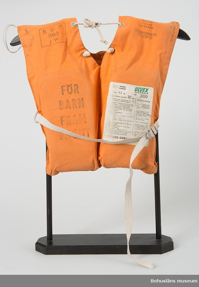Flytväst för barn upp till 30 kilo. Modell utan rygg i orange bomullstyg med kraftig krage med flytelement. Västen träs över huvudet.  Ett kraftigt vävt band med metallspänne för knäppning runt magen. Snörknäppning i halsen. På höger framsida tryckt text: FÖR BARN FRAM FRONT På baksidan ytterligare tryckt information FÖR BARN FRAM FRONT ULVEX 2030 K. SJÖFARTSST. OLJEBESTÄNDIG STYROPOR Vit tygetikett fastklistrad inuti med VDN-fakta, säkerhetsinstuktioner och uppgifter om bärighet och storlek samt skötselanvisningar. [oläsligt]VSUNDA GUMMIFABRIKS AB BROMMA Svarta mögelfläckar.