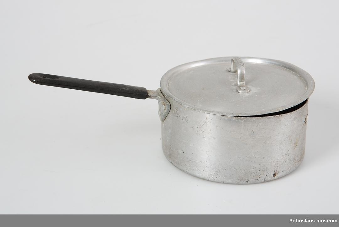 Aluminiumkastrull, 1 L,  med lock med handtag av svart hårdplast, bakelitliknande. Deformerad och i botten missfärgning efter gasolkökets låga.