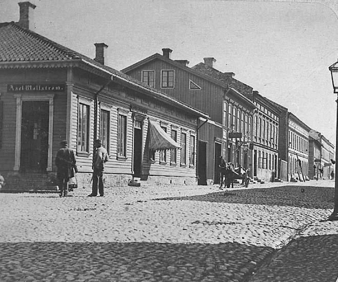 """Text på kortet: """"Kungsgatan, Uddevalla, österut från """"Hallmans hörna"""", 1860-talet""""."""