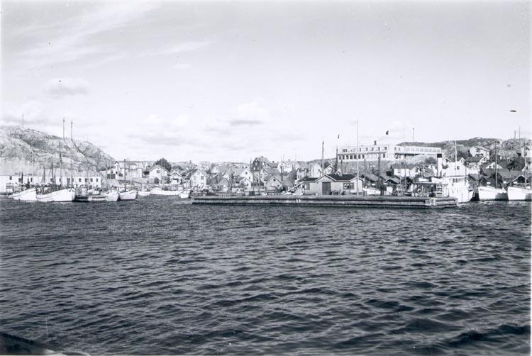 """Notering på kortet: """"Gravarne. Hamnbild ca. 1950. I förgrunden ångbåtsbryggan""""."""