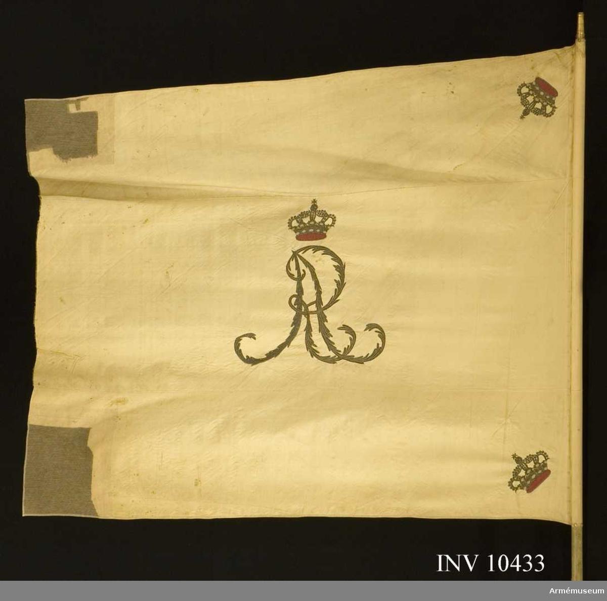 Grupp B.  Fanduk av vit sidenkypert, varå broderat i guld omvänt lika å båda sidor, i mitten Gustav IV Adolfs namnchiffer GA under sluten kunglig krona, med ytter- och innerfoder i rött silke samt stenar i olikfärgat silke, allt 52 cm högt. I hörnen slutna kungliga kronor liknande namnchiffrets, kantad med vitt sidenband, fäst med vitt sidenband och förgyllda spikar. Stång 276 cm, avsågad. Holk 8 cm.