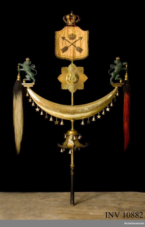 Grupp B. Janitscharspel, turkisk halvmåne, Muhammedsfana. Består av en mässingsstång med svart träskaft och på denna sitta, uppifrån räknat:1. Kungl. krona. 2. en gul sidenduk med guldtrådkant; på duken är broderat Dalarnes vapen (två pilar) med Kungl. krona över; 3. en måne av mässing med lyra i mitten och strålar omkring; 4. en större (dubbel, ihålig) månskära av mässing, som på vardera spetsen, på en platta, har två upprätt stående, grönbronserande lejon med Kungl. kronor på huvudena; i lejonens tassar hänga hästtagel, svart på den ena och rött på den andra; på månskärans konvexa undersida hänga, omväxlande varannan, 10 små bjällror och åtta stjärnor, alla av mässing; 5. en stor meäsingsklocka, utan kläpp, med genombruten, lövformiga väggar; på klockan hänga upptill sex små bjällror och två femuddiga stjärnor, alla av mässing, samt nedtill fjorton små bjällror av mässing (några fattas numera). Bärrem av svart läder. Tillhört Kungl. Dalregementets musikkår. Höjd 2100 mm. Största bredd 1200 mm. 18890529 putsat. / Aug. 1939. A Lilliehöök.