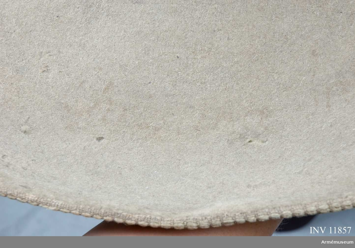 """Grupp C I.  Modellhatt för drottning Kristinas infanteri. Tillverkad vid 1600-talets mitt. På brättets ovansida finns en, något synlig, inpressad text: """"Prof Hatt för Drottning Christinas Infanterie"""".   Kulle: diameter 250 mm, omkrets vid basen 615 mm. Diameter med brätte: 530 mm.  Brätte: bredd 180-185 mm på ovansidan, omkretsen i ytterkant är 1630 mm.  Hatten är tillverkad av stampad filt i beigegrå färg. Runt brättets ytterkant, på undersidan, är ett mönstrat band av ull och lin, b:25 mm, påsytt."""